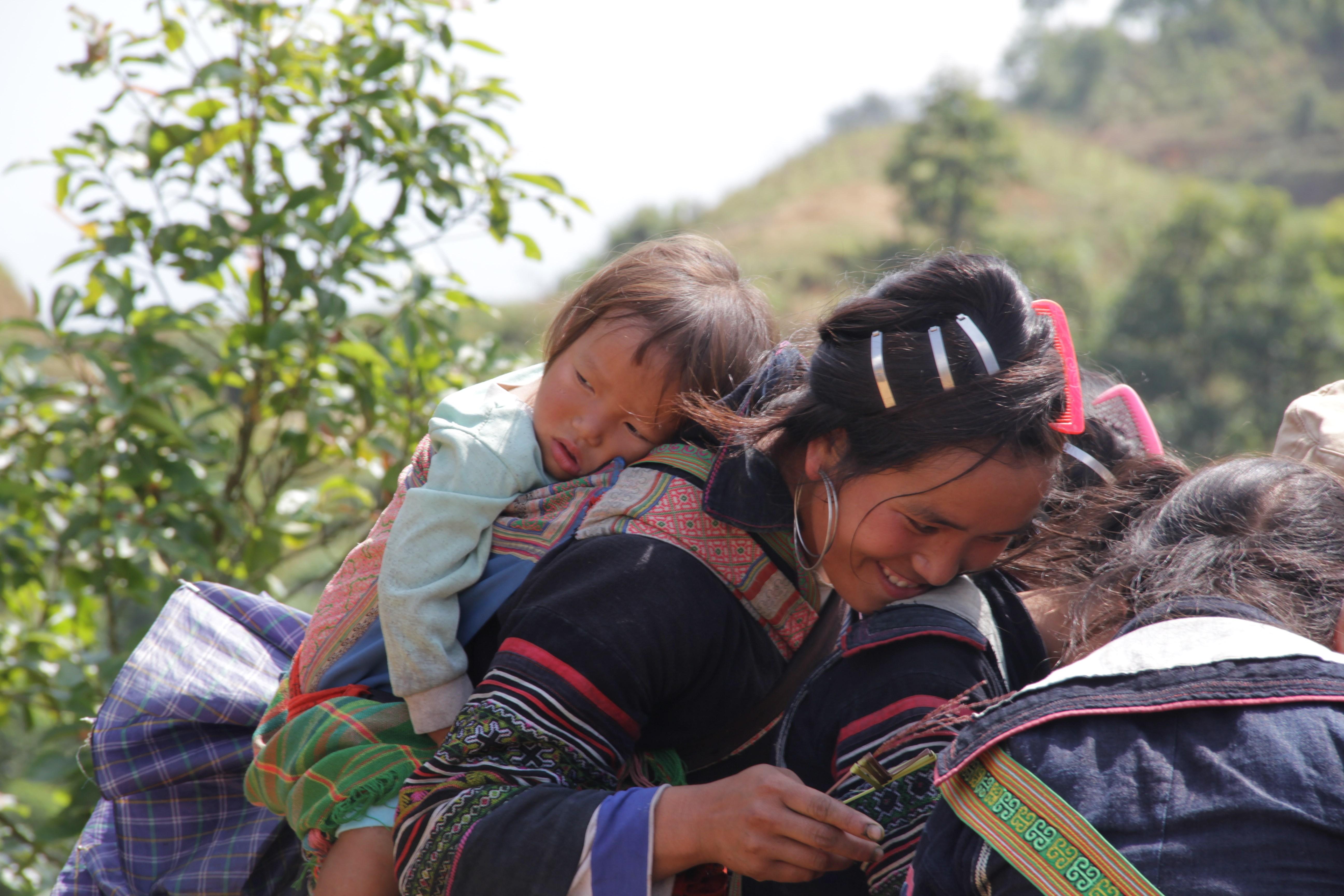 Les H'mong marchent avec leur enfant sur le dos. (© Jérôme Decoster)