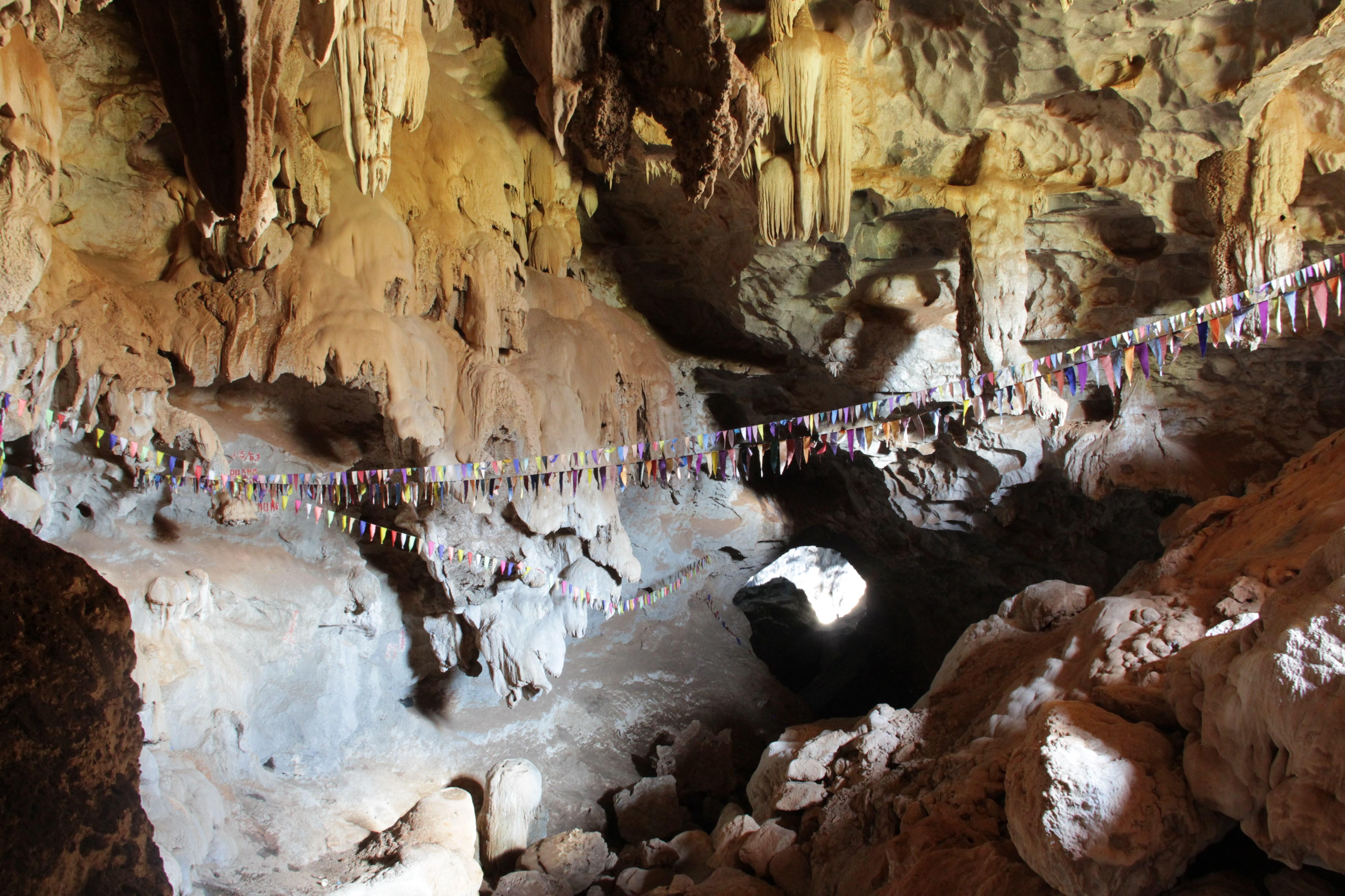 Comme plusieurs grottes, celle de Pha In sert de lieu de prière aux bouddhistes, qui l'ont ornée d'une guirlande de petits drapeaux (© Aurélie Bacheley).
