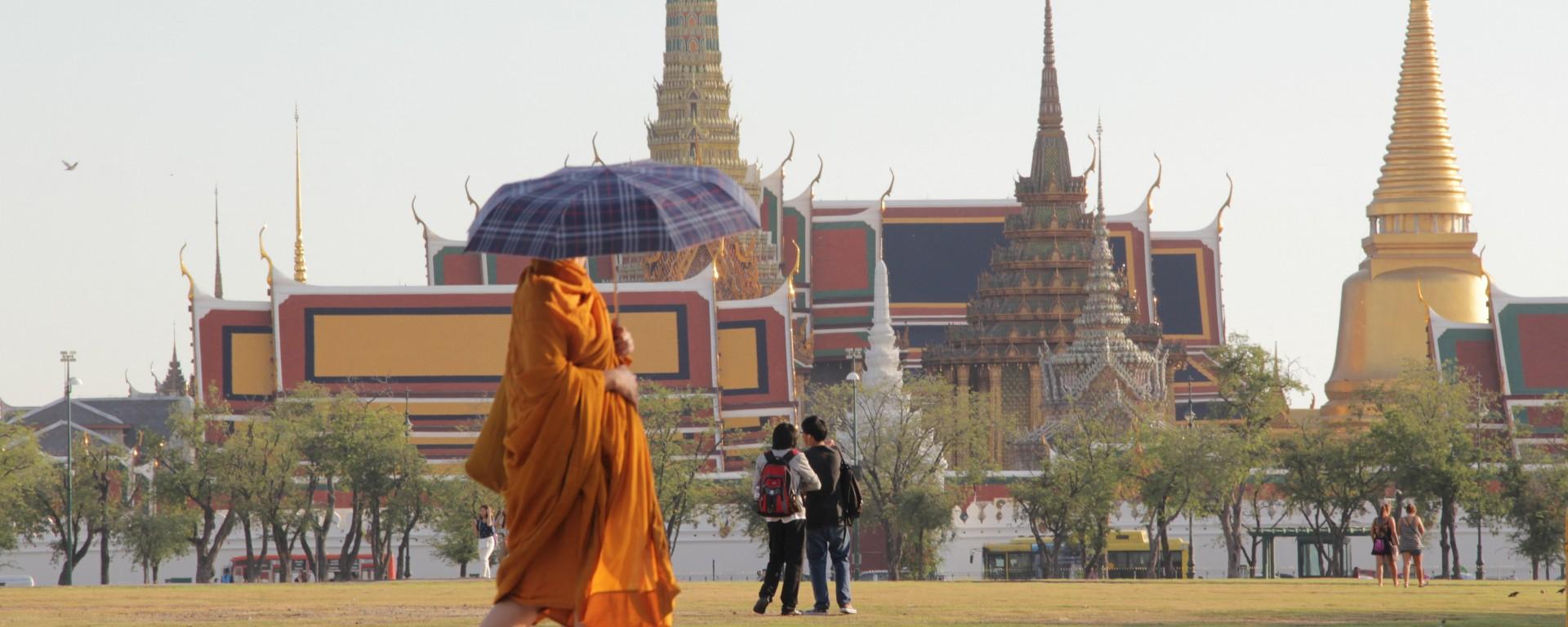 Un moine devant le haut lieu touristique de Bangkok : le temple Wat Phra Kaew et le grand palace (© Jérôme Decoster).