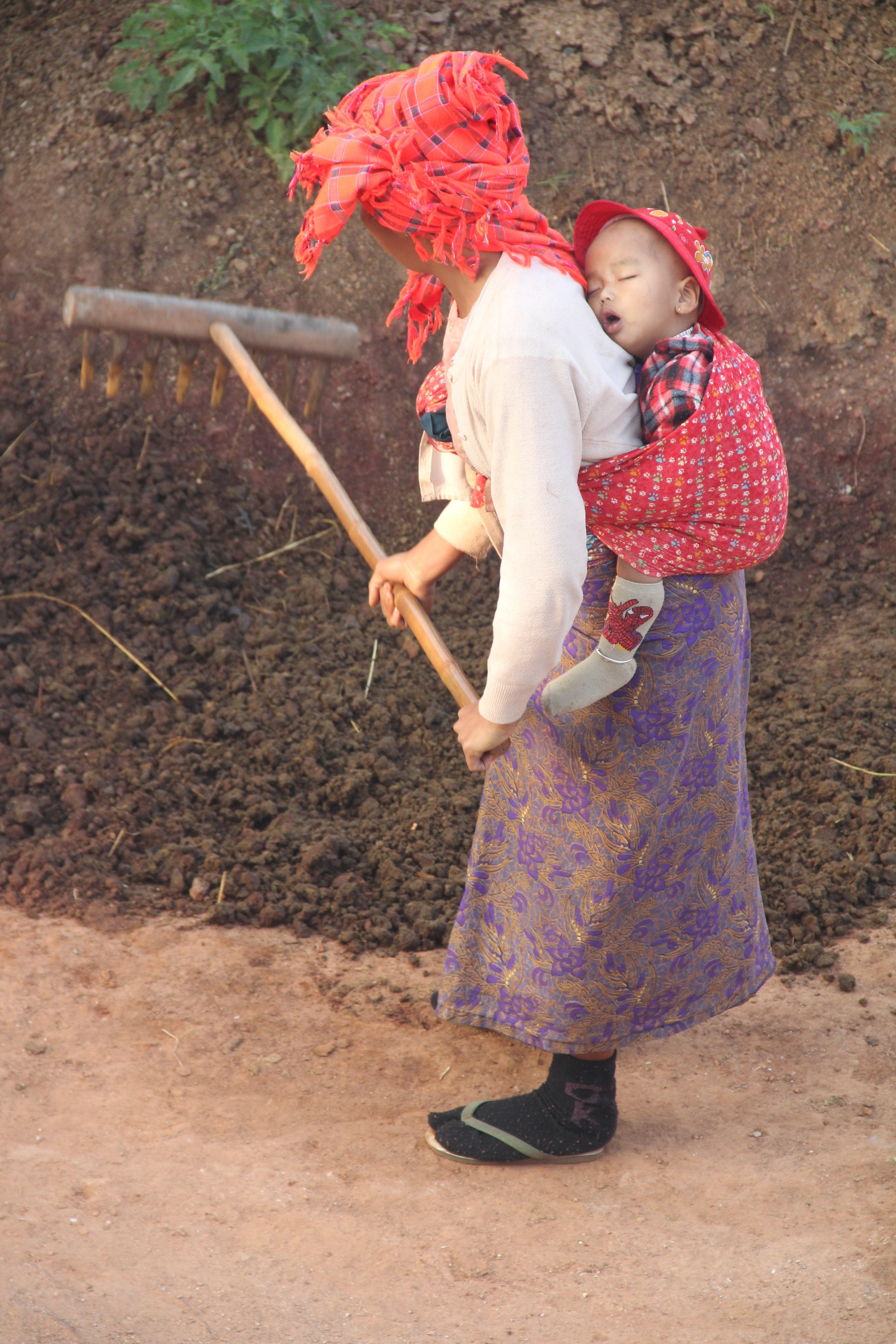 Devant sa maison, une femme travaille la terre avec son bébé sur le dos (© Aurélie Bacheley).
