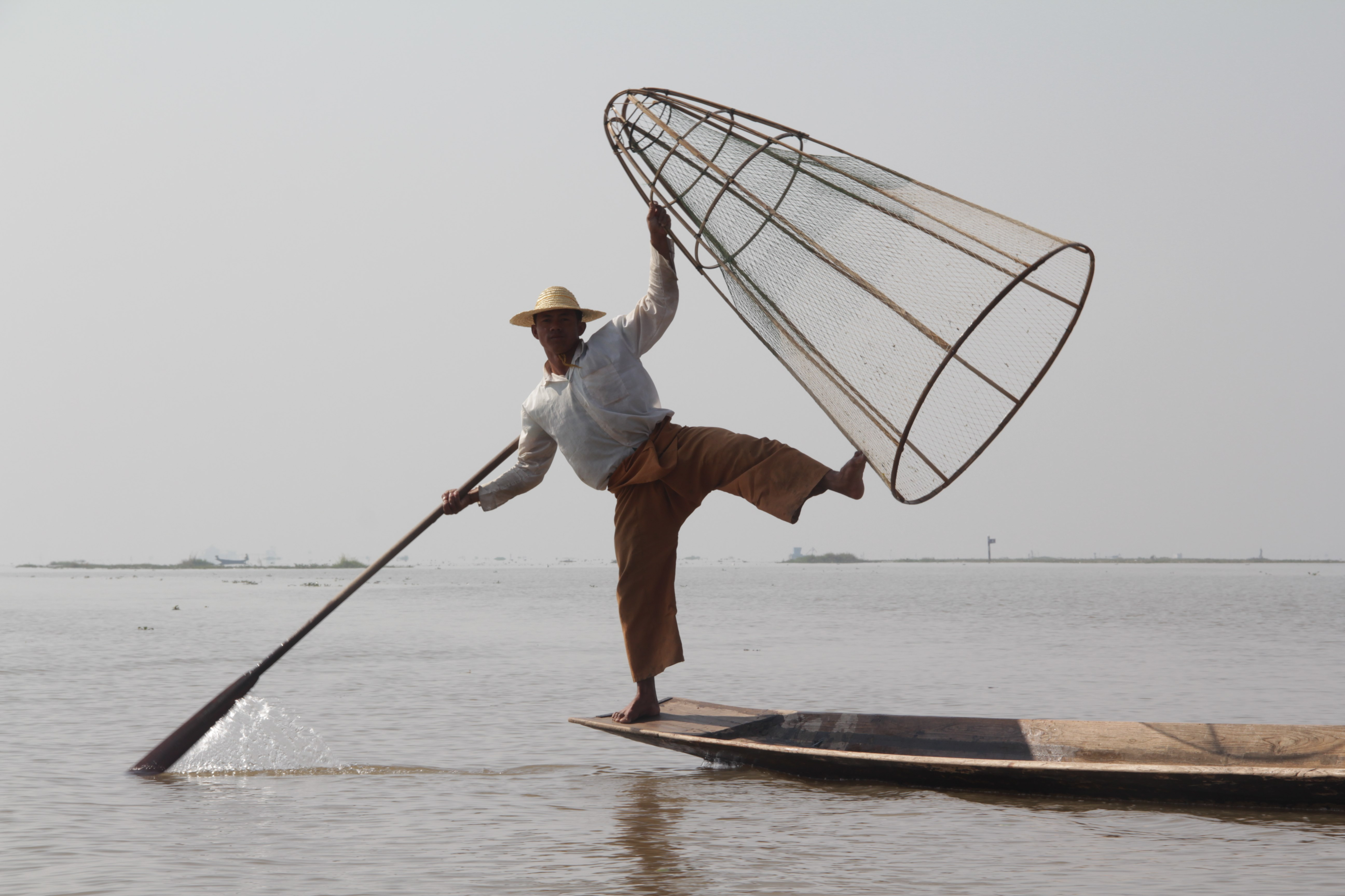 Pagaie au pied pour se diriger et filet à la main, les pêcheurs du lac Inle ont une allure de danseurs professionnels (© Jérôme Decoster).