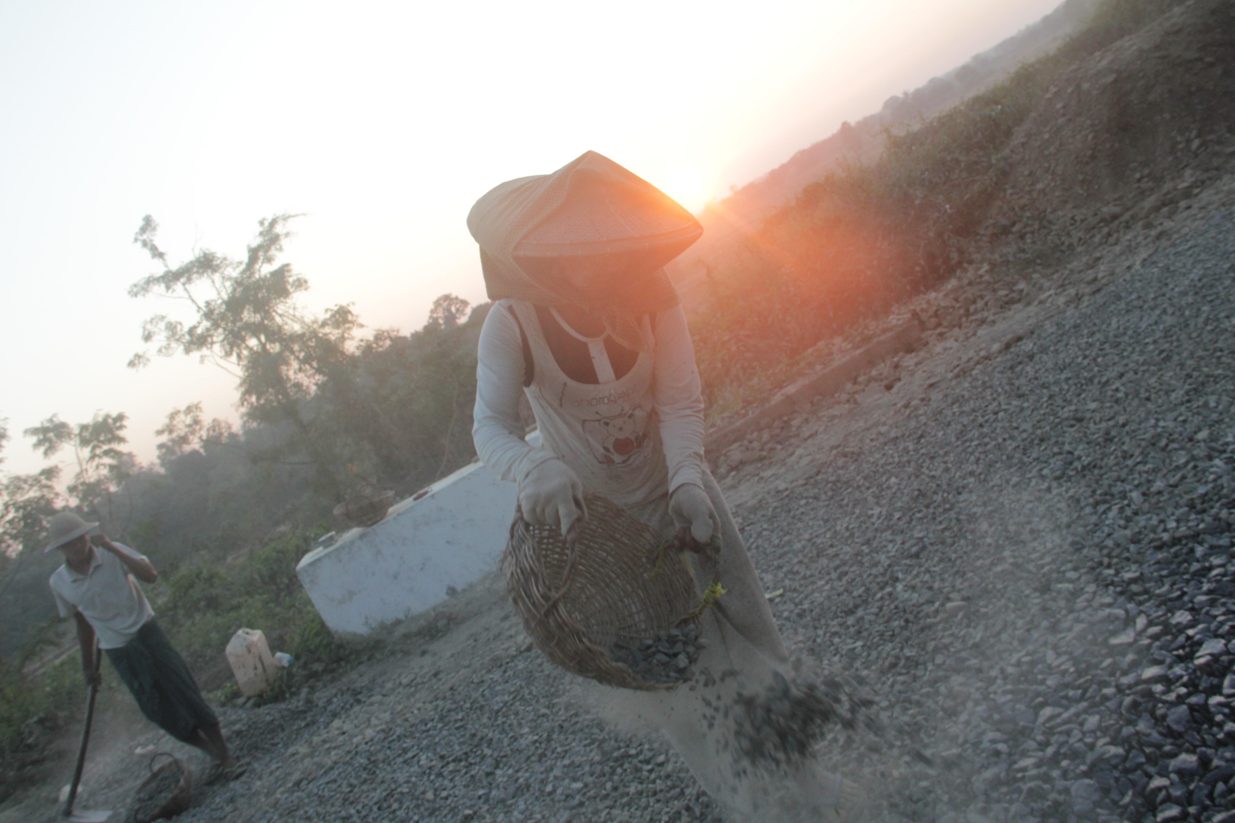 Cette femme s'affaire à étaler des cailloux sur la route pour la goudronner (©Jérôme Decoster).