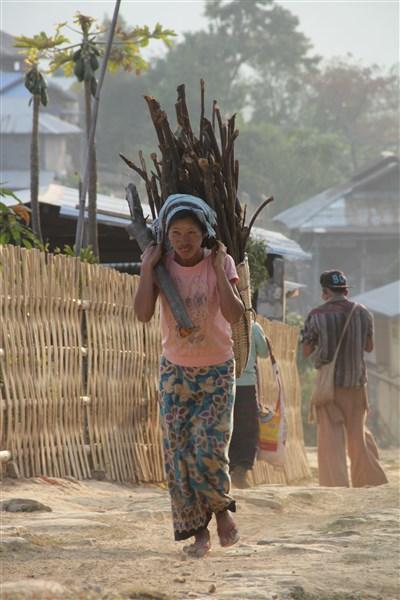 Dans le village de Tan Sent, les femmes portent des paniers en bambou chargés de bois (© Jérôme Decoster).