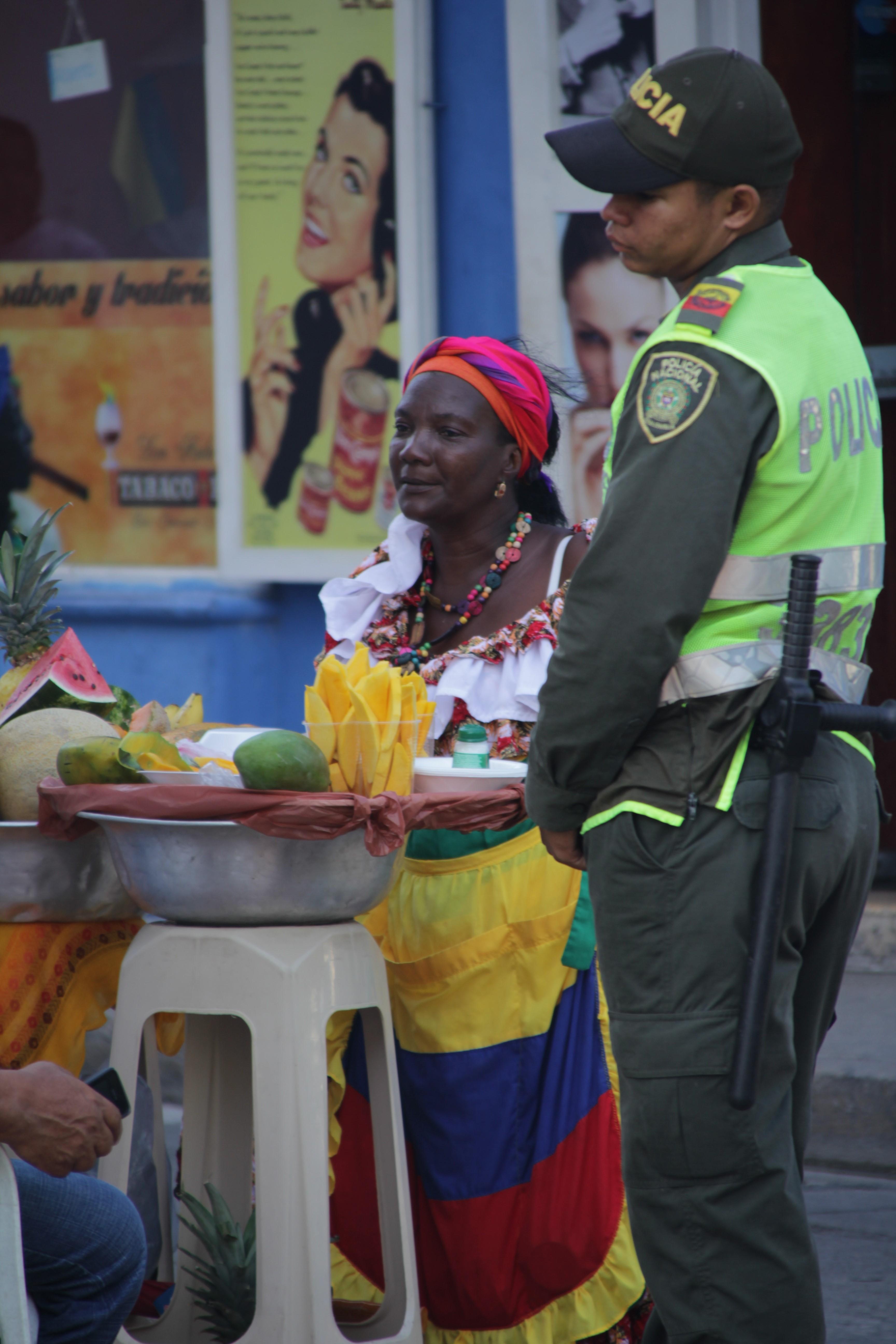Une femme vend des fruits découpés aux côtés d'un des nombreux policiers présents dans le centre (© Jérôme Decoster).