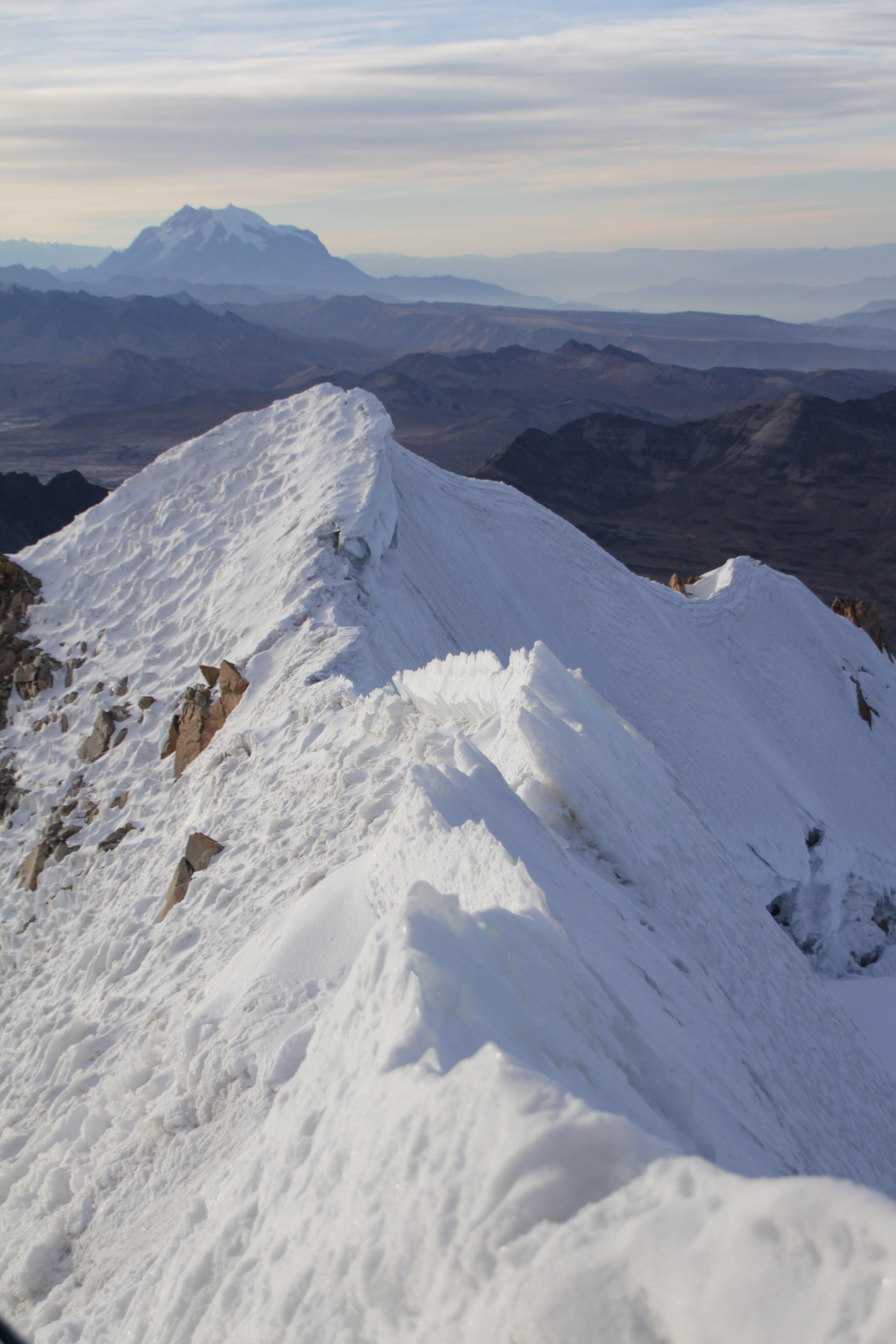 Au sommet, avec en toile de fond un autre géant andin, l'Illimani (© Jérôme Decoster).