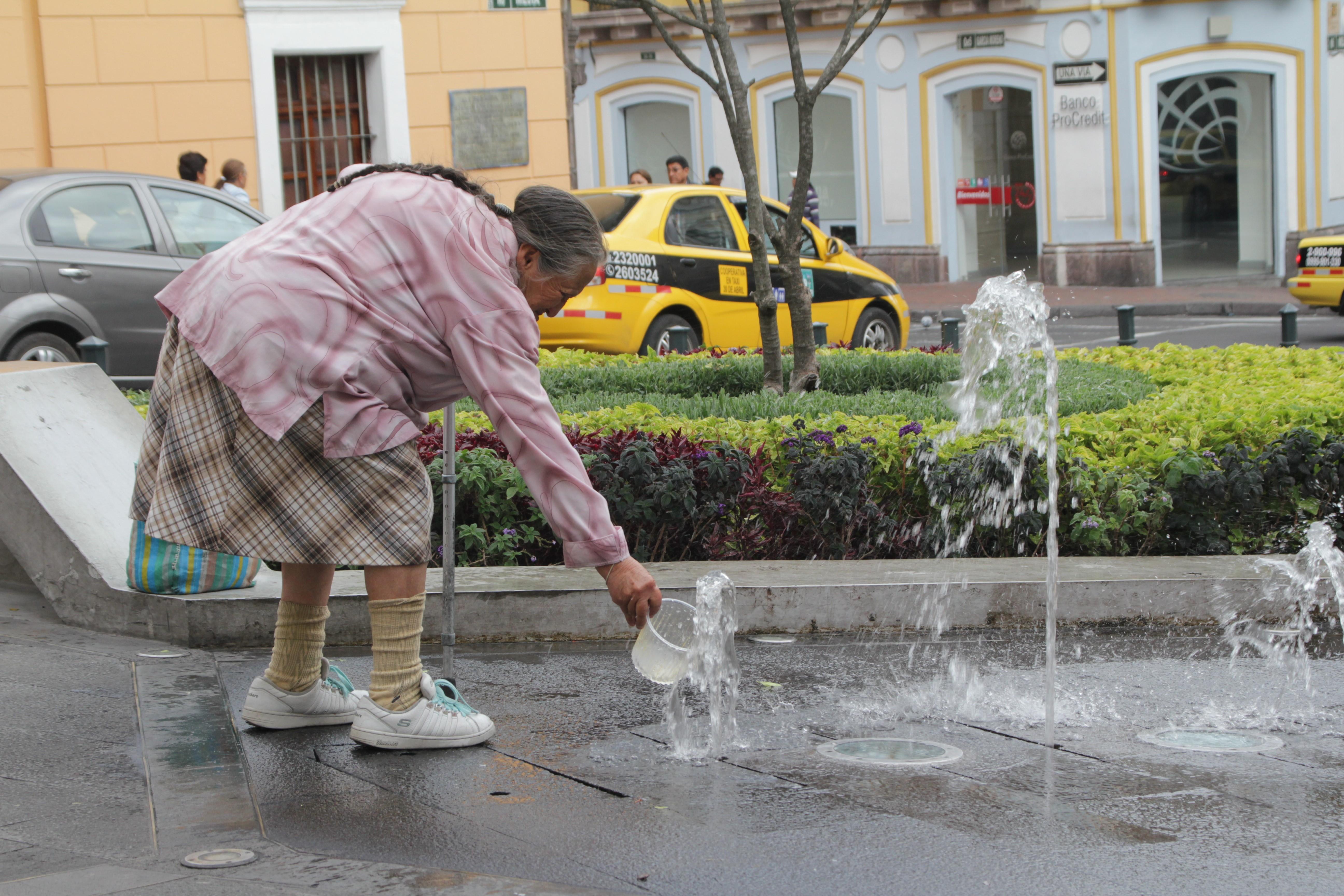 Une femme récolte l'eau de la fontaine où jouent les enfants (© Jérôme Decoster).
